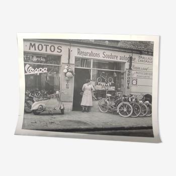 Une photo :concessionnaire vespa et motos. gros plan  sur magasin vers  1960