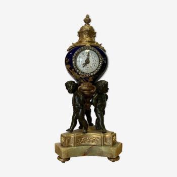 Pendule aux putti en bronze a deux patine et porcelaine vers 1900