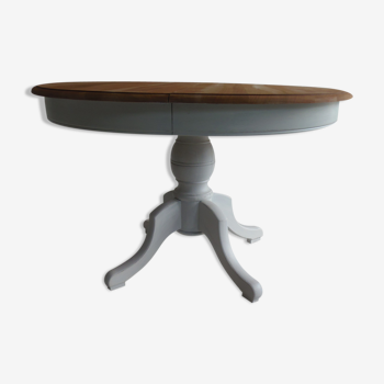Table ronde avec rallonges piètement central et ceinture patinés gris perle, plateau bois.