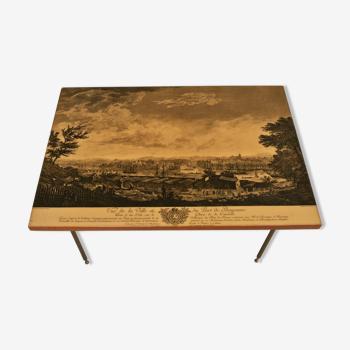 Table basse - plateau en bois laqué à décor de la ville de Bayonne - pieds gaudronnés en laiton