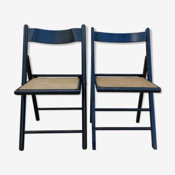 Paire de chaises pliantes en bois noirci et assise cannée
