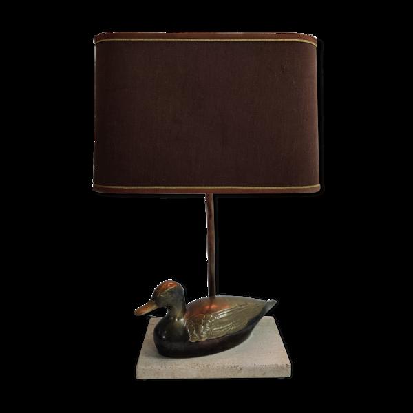 Lampe de table avec socle en travertin sur lequel repose un canard en laiton