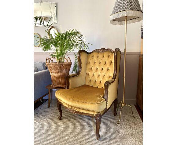 Fauteuil bergère en velours jaune capitonné vintage